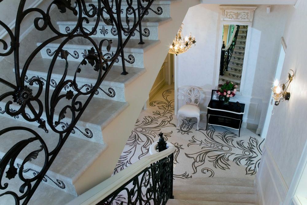 Орнамент кованого лестничного ограждения рифмуется с узором мозаики.