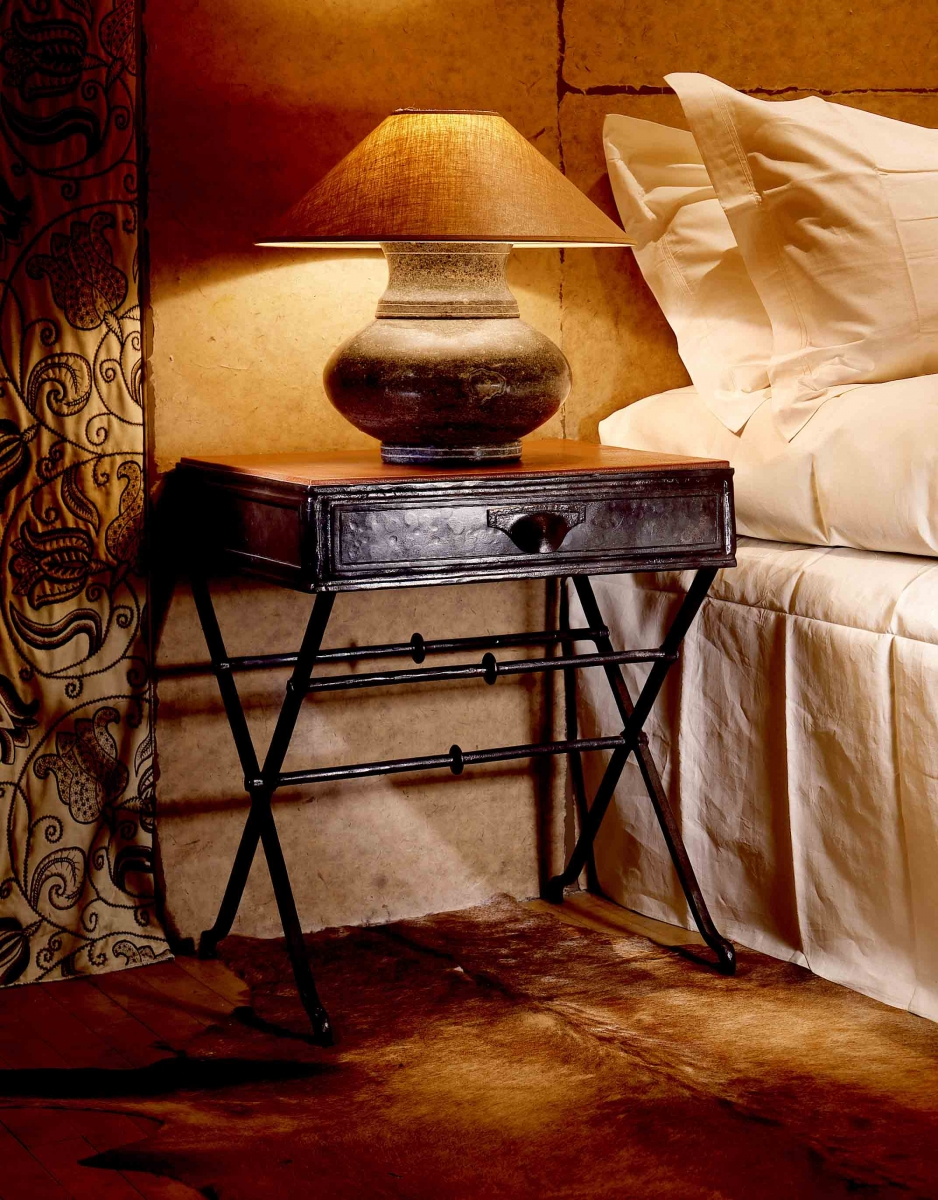The Cavaletti Bedside Table is handmade by Soane's blacksmith at his workshop on the Gloucestershire-Welsh borders.  The forged iron frame has neat joint details and subtly 'hoofed' feet that firmly ground the table.  The hand beaten top is skillfully welded together, with panel details and a hammered pull handle on the drawer adding to its character.  A choice of drop in top is offered, each made by Soane's specialist craftsmen.