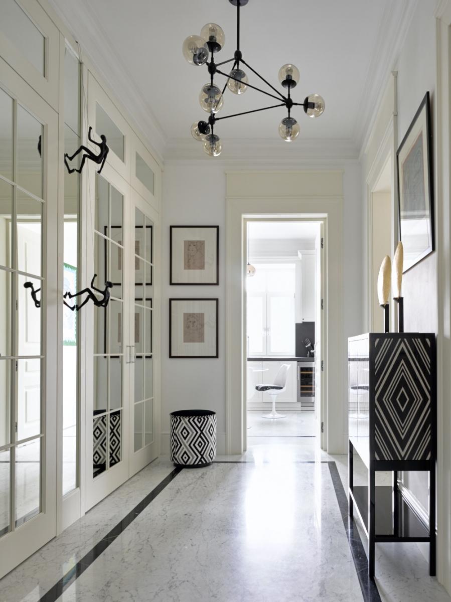 Лаконичная белая прихожая в нашем исполнении. За зеркальной стеной спрятаны дверь в санузел и два шкафа.<br />Проект Анны Муравиной.