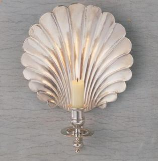 This elegant and dramatic wall light with its softly scalloped back plate reflects light magically.  The Shell Wall Light works well in any room and can be electrified, or looks romantic with candles.  This light is handmade and can be finished in a variety of metals to suit any interior. The Shell Wall Light is available in two sizes.